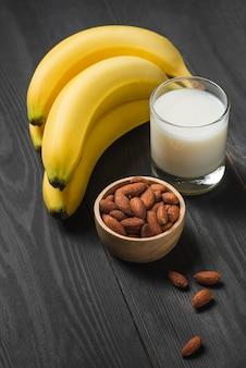 木製の背景にアーモンドとミルクとバナナの束。