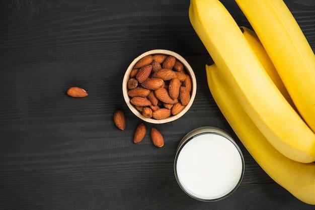 나무 배경에 아몬드와 우유를 넣은 바나나 한 무리.