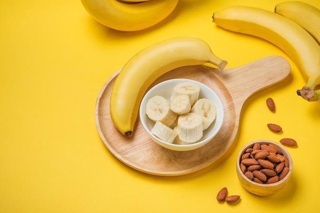 Банч бананов с миндалем на желтом фоне.