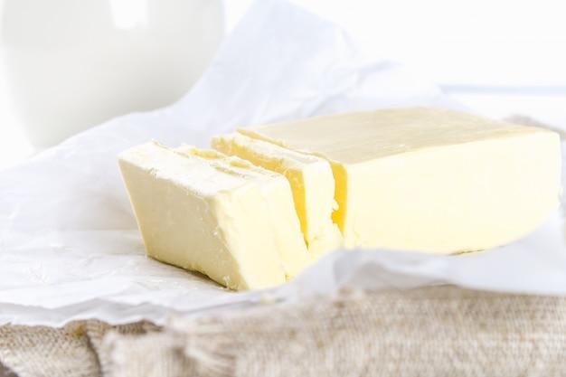 白いテーブルの上のナイフで木の板にバターのバー。料理の食材