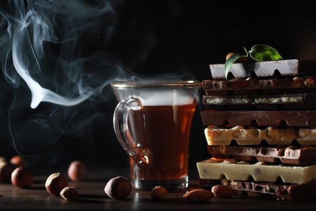 ミルクチョコレートのバー。アーモンドと乾燥イチゴを使った自家製ミルクチョコレート。ミルクチョコレートのかけら。ラベルのないミルクチョコレートバー。お茶とチョコレートのセット。