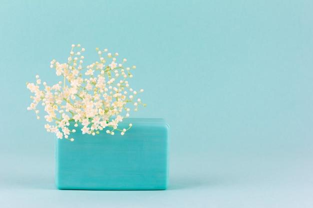 복사 공간이 파란색 배경에 흰색 작은 꽃으로 수제 비누 바