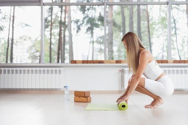 裸足の女性が寄木細工の床で緑のヨガマットとフィットネスをひねります