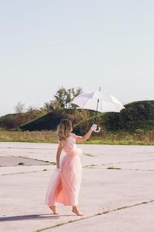 쉬폰 드레스를 입은 맨발의 소녀가 하얀 우산 아래에서 산책
