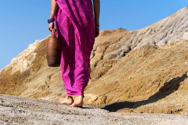 Босая женщина в этнической одежде несет в руке глиняный кувшин.