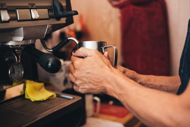 コーヒーメーカーでカプチーノを準備するバリスタ