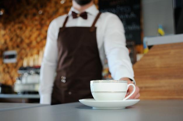 ホットコーヒーのカップとバリスタ