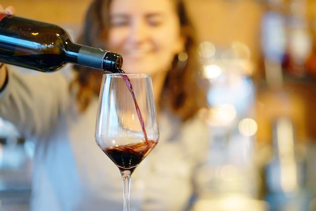 Девушка-бармен, улыбаясь, наливает красное вино в бокал из бутылки. сосредоточьтесь на стекле