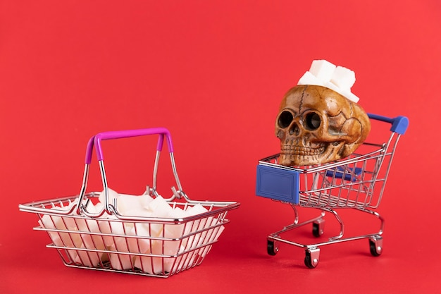 赤い背景に人間の頭蓋骨が付いた洗練された砂糖の立方体で満たされたバスケット。スペースをコピーします。
