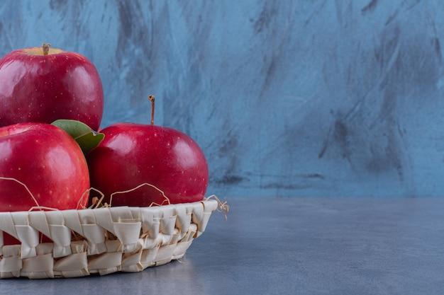 어두운 표면에 사과와 잎 바구니