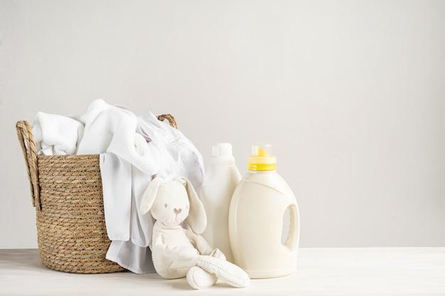 흰색 세탁 바구니, 테디 버니 장난감, 액체 세제 한 병, 세탁 젤 또는 섬유 유연제. 복사 공간이있는 아기 옷을 씻는 모형.