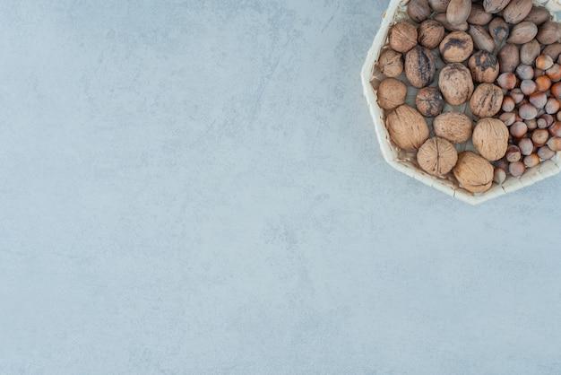 대리석 배경에 건강한 견과류와 바구니입니다. 고품질 사진