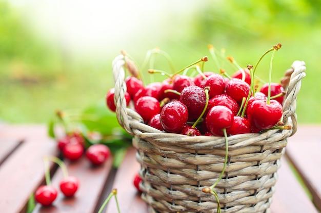 木製のテーブルの上に熟した果物が入ったバスケット。夏の収穫ベリーのクローズアップ。健康的な食事のためのオーガニックのダイエット食品。