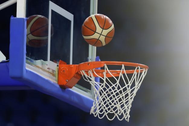 На ринг влетает баскетбольный мяч. на фоне спортивного комплекса