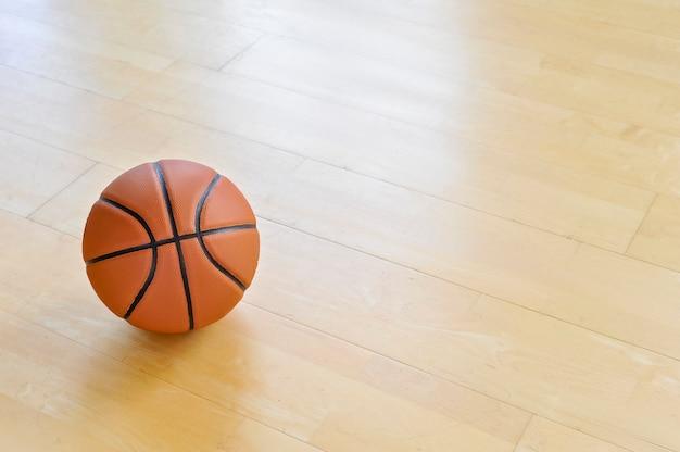 背景として木の床のバスケットボール。チームスポーツの概念