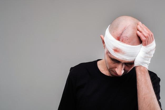 黒のtシャツを着たボロボロの男が灰色の背景に立ち、痛む頭を両手で包んで保持している