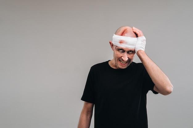 Измученный и избитый мужчина в черной футболке стоит на сером фоне, обхватив больную голову руками.