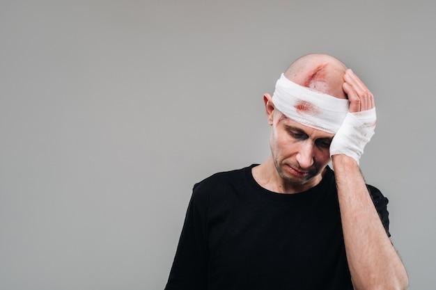 黒のtシャツを着たボロボロの男が灰色の背景に立ち、痛む頭を両手で包み込んでいます。