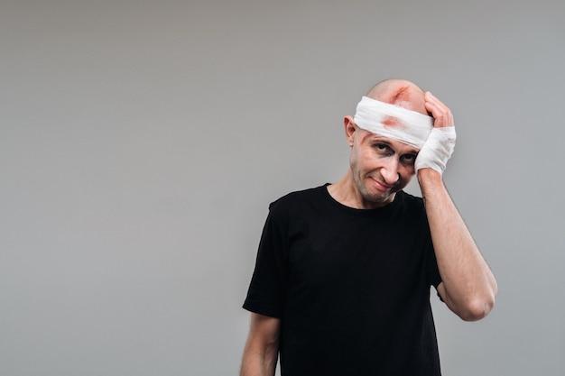 У серой стены стоит избитый мужчина в черной футболке, держась за ноющую голову.