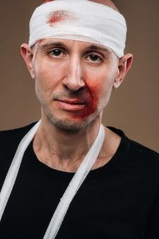 包帯を巻いた頭と彼の腕にギプスを持つボロボロの男は灰色の背景に立っています
