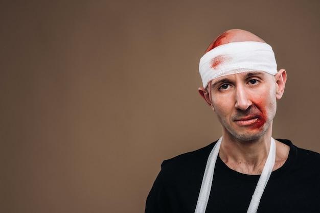 На сером фоне стоит избитый мужчина с забинтованной головой и гипсом на руке.
