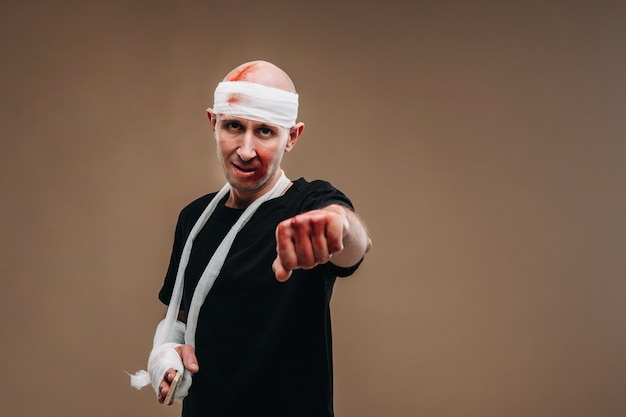 包帯を巻いた頭と腕にギプスを巻いたボロボロの男が灰色の背景に立っています。