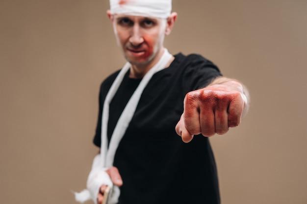 包帯を巻いた頭と腕にギプスを巻いたボロボロの男が灰色の壁に立っている