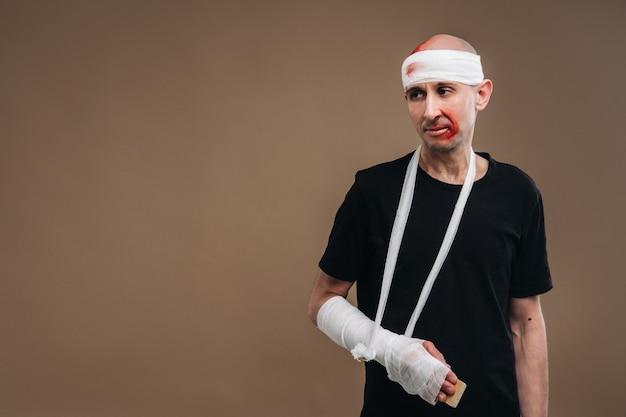 Избитый мужчина с забинтованной головой и гипсом на руке стоит на костылях на сером фоне.