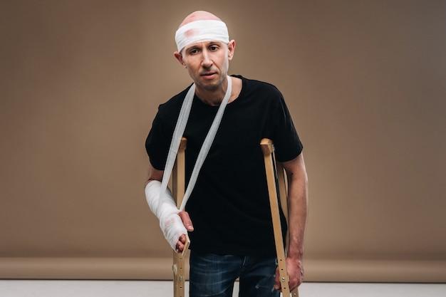 松葉杖の上に、包帯を巻いた頭と腕にギプスを巻いたボロボロの男が立っている