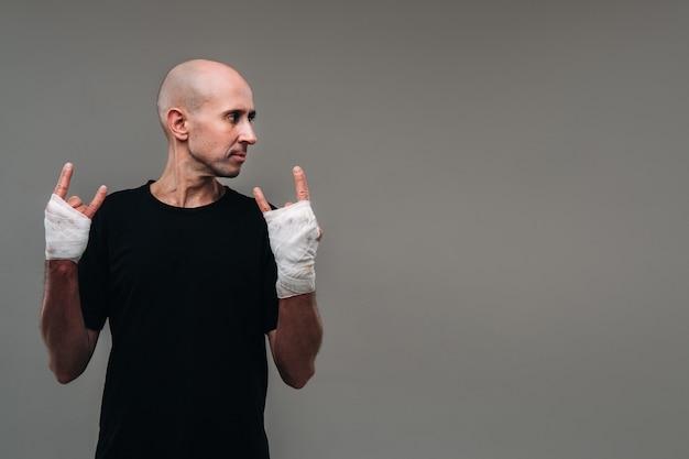 마약 중독자와 술에 취한 사람처럼 보이는 회색 표면에 검은 색 티셔츠를 입은 손으로 폭행당한 남자.
