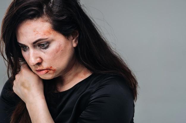 고립된 회색 배경에 검은 옷을 입은 폭행당한 여자. 여성에 대한 폭력.