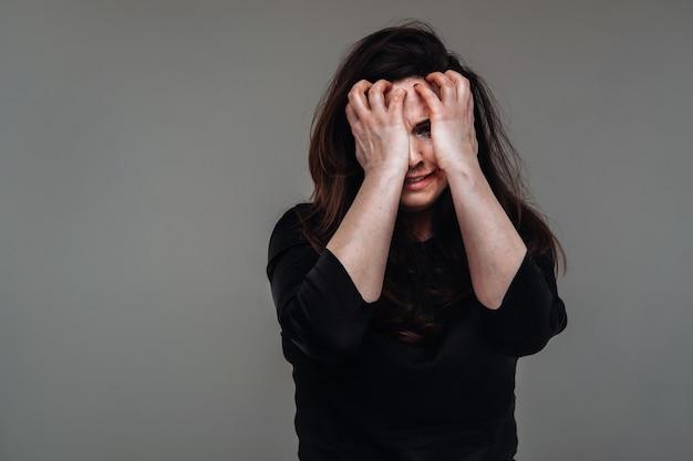 격리 된 회색 배경에 검은 옷에 폭행 된 여자. 여성에 대한 폭력
