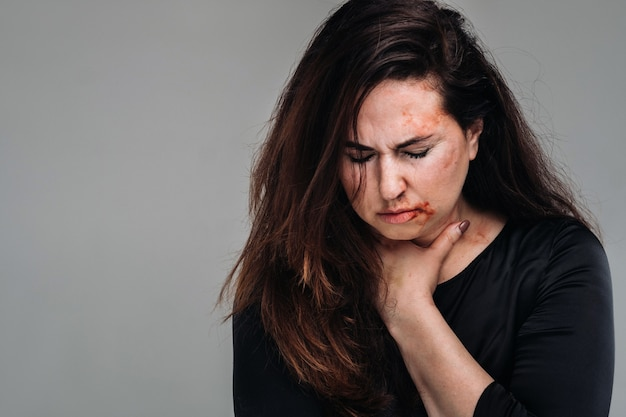 고립된 회색 배경에 검은 옷을 입은 폭행당한 여자. 여성에 대한 폭력 프리미엄 사진