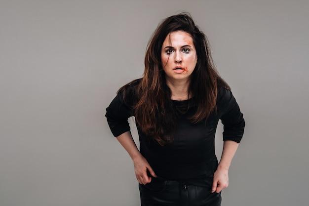 고립된 회색 배경에 검은 옷을 입은 폭행당한 여자. 여성에 대한 폭력