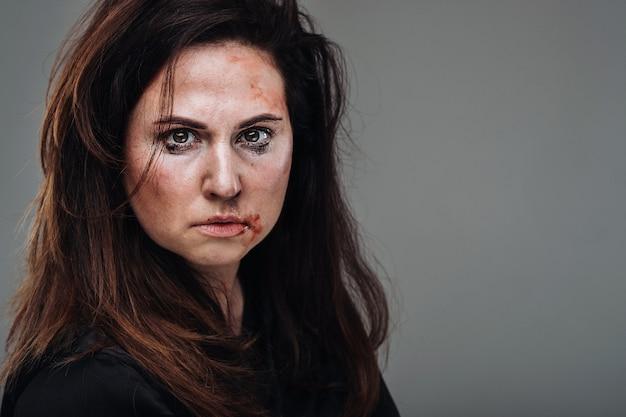 격리 된 회색 벽에 검은 옷에 폭행 된 여자. 여성에 대한 폭력.