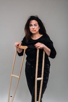 灰色の壁にキャスターを手にした黒い服を着た虐待を受けた女性