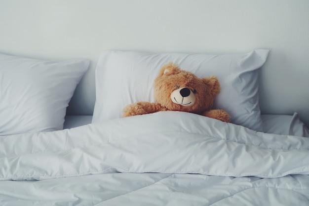 Медвежья кукла, лежащая на белой кровати