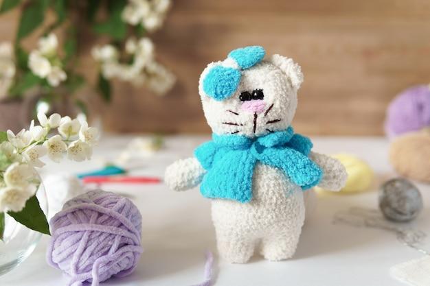 羊毛糸でできたクマ。木製のテーブルの上に手作りのニットぬいぐるみ。