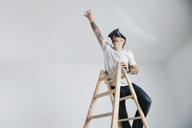 Бородатый и татуированный молодой человек в белой футболке без надписи и очках виртуальной реальности стоит на лестнице и тянется к чему-то