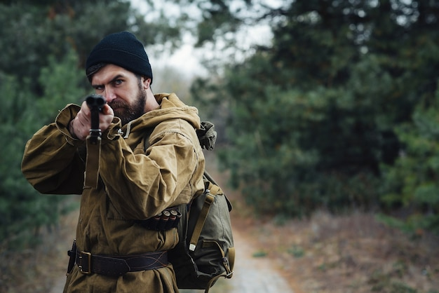카트리지와 녹색 배낭이 달린 검은 모자와 카키색 재킷을 입은 수염 난 잔인한 남자 사냥꾼