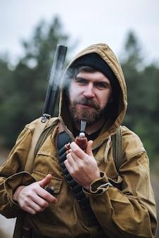 어깨에 총이 있고 가슴에 카트리지가있는 카키색 재킷의 후드에 검은 모자를 쓴 수염 난 잔인한 남자 사냥꾼이 파이프를 피우고 라이터를 들고