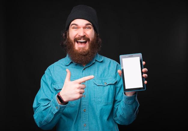 Бородатый веселый мужчина держит взволнованный планшет и, указывая на него, смотрит в камеру