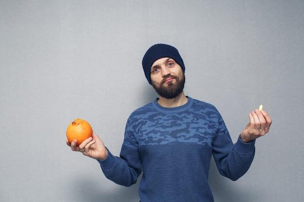 Бородатый парень держит в руках апельсин и суппозиторий от геморроя. концепция геморроя.