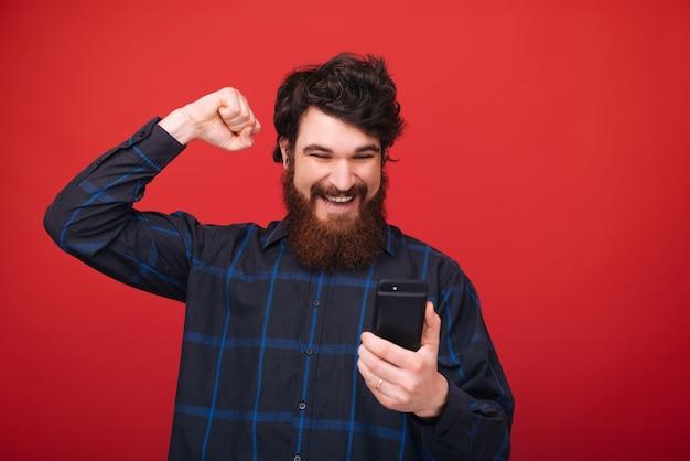 Бородатый парень над красной стеной, используя смартфон и поднимая руку, как победный жест