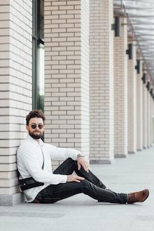 수염이 있고, 행복하고, 웃고, 세련된 남자가 현대적인 사무실 센터 근처의 거리에서 흰 셔츠를 입고 밀가루 위에 앉아 있다