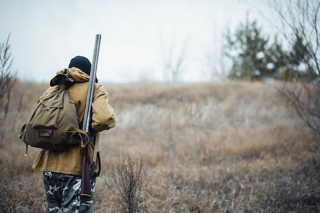 Бородатый мужчина-охотник в темной теплой шапке, в куртке цвета хаки и камуфляжных штанах с ружьем на плече