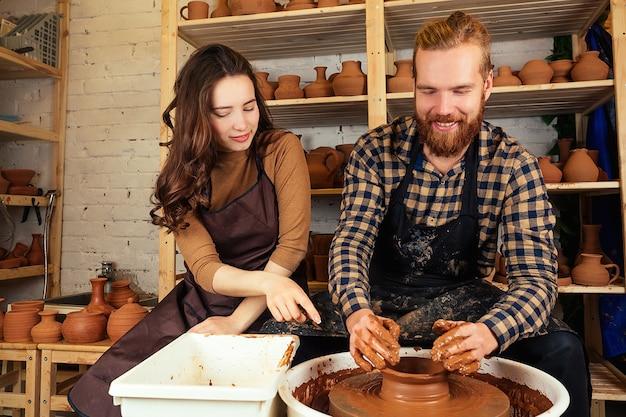 Бородатый мужчина и молодая женщина лепят на гончарном круге глиняную вазу возле стеллажа с вазами и горшками из глины. гончар, глина, ваза, гончарная мастерская. магистр и ученик.
