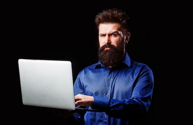 ひげを生やした男は彼の手でラップトップを保持しています。