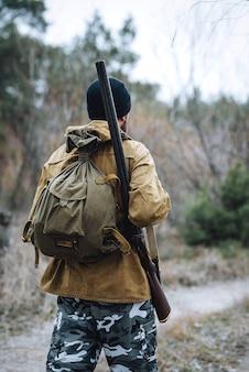 Бородатый мужчина-охотник в темной теплой шапке в куртке цвета хаки и камуфляжных штанах с ружьем на плече
