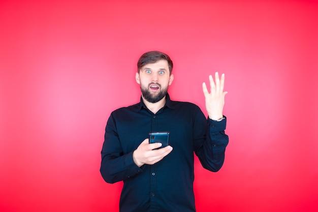 黒のシャツを着たあごひげを生やした男性が携帯電話を手に持って、感情的にジェスチャーをします。赤い背景のひげを生やした男